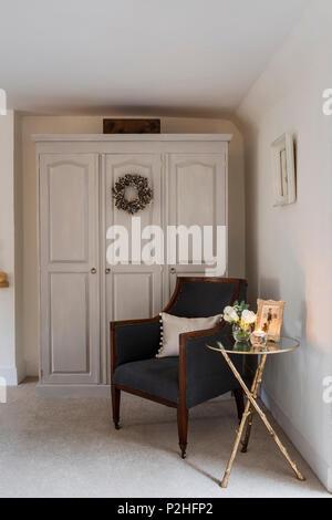 Silla tapizada en antigüedades Ian Mankin el Chelsea Tejido gris marengo en la esquina del dormitorio. La tabla es de Graham Green y el armario pintado en Pur