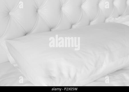 Cerca almohada blanco sobre blanco, cama de lujo. Foto de stock