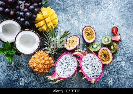 Grupo de exóticas frutas tropicales. El mango, fruta del dragón, fruta de la pasión, coco, kiwi, piña y fresa sobre fondo azul de hormigón. Fruta fresca