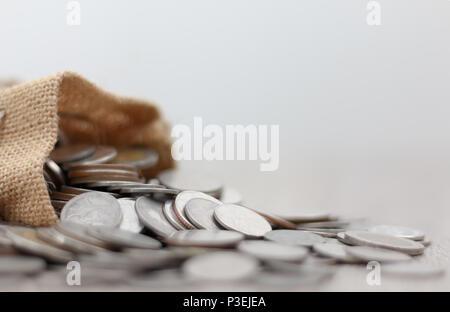 Monedas en el saco sobre la mesa de madera con espacio de copia. Seleccione focus gran profundidad de campo y el fondo borroso.