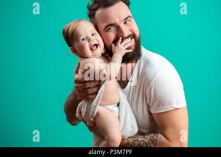 Juguetón padre llevar a su niño sonriente en cuello sobre fondo azul.