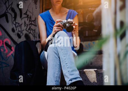 Mujer joven sentada en las escaleras, sosteniendo la cámara vintage y mirando a las fotos hechas en el tour por la ciudad