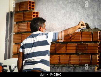 Em construção Pedreiros levantando parede de tijolos.