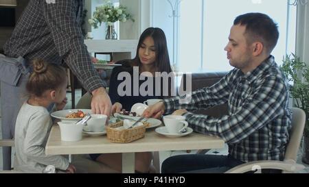Camarero trayendo pasta a little pretty girl cenando con su familia en el restaurante. Sus padres han comido sus ensaladas todavía.