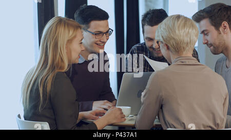 Tripulación del talentoso equipo de negocios masculinos y femeninos descansa divirtiéndose y bromeando durante el descanso de trabajo