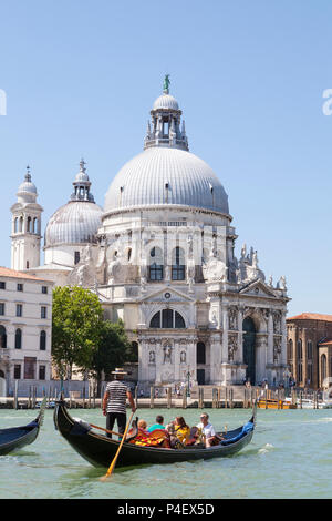 Las góndolas con turistas en frente de la Basílica di Santa Maria della Salute, el Grand Canal, Dorsoduro, Venecia, Véneto, Italia en las primeras horas de la mañana la luz