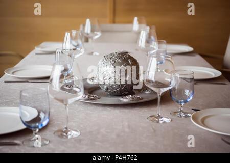 Ver de cerca la disposición de cubertería, decoraciones y wineglasses vacía sobre la mesa en el restaurante