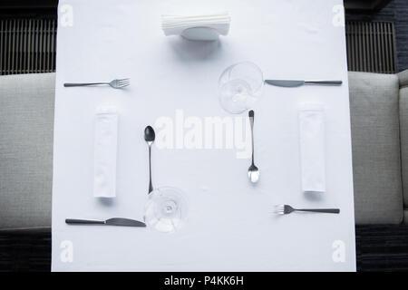 Vista superior de la cubertería y wineglasses dispuestas sobre la mesa con mantel blanco en restaurante.