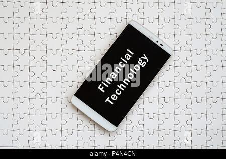 Un moderno gran smartphone con pantalla táctil se encuentra en un blanco rompecabezas en un estado armado con la inscripción. La tecnología financiera Foto de stock