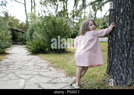 Retrato de niña RECOSTADA contra el tronco del árbol en el jardín