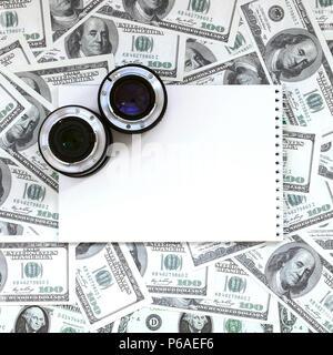 Dos lentes fotográficos y portátil blanco yacen en el fondo de un lote de billetes de dólar. Espacio para el texto . Foto de stock