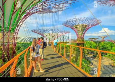 Singapur - Abril 29, 2018: Asia toma selfie turística con teléfono inteligente mientras camina sobre el puente Skyway de Supertree OCBC O Grove en los jardines junto a la bahía Marina Bay, en Singapur.