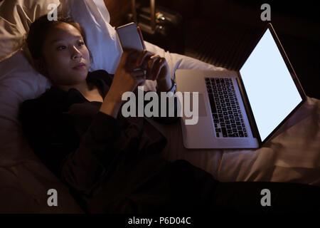 Bella mujer utilizando el teléfono móvil mientras se relaja en la cama Foto de stock