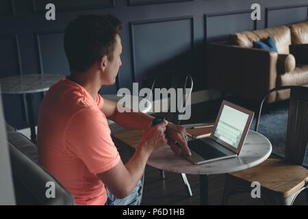 Empresario utilizando smartwatch en la cafetería