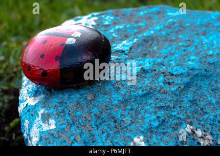 Un insecto llamado mariquita está hecha de piedra y pintado de sus tintas. La cifra se sitúa en el jardín en una piedra azul. Muy bonito e interesante h