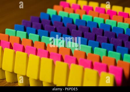 Filas de gomas de borrar o borradores de los lápices de colores brillantes alineadas en un TOC ordenada con una iluminación uniforme y contrastand una moderada profundidad de campo.