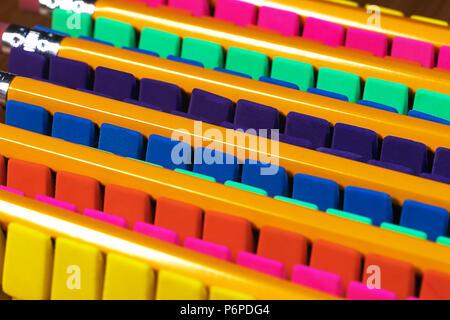 Filas de gomas de borrar o borradores de los lápices de colores brillantes alineadas en un TOC ordenada, con lápices sentando a través de ellos. Iluminación de alto contraste y alta vitalidad