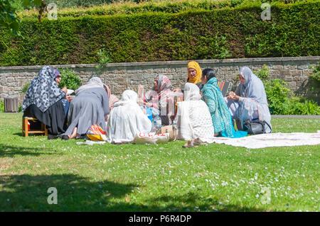 Glasgow, Escocia, Reino Unido. El 2 de julio, 2018. El clima del Reino Unido: un grupo de mujeres asiáticas, sentados en el césped, haciendo un picnic en una tarde soleada en Pollok Country Park. Crédito: gorro/Alamy Live News Foto de stock