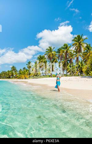 Canto de la playa, Isla Saona, East National Park (Parque Nacional del Este), en la República Dominicana, Mar Caribe. Bella mujer en una playa llena de palmeras (MR).
