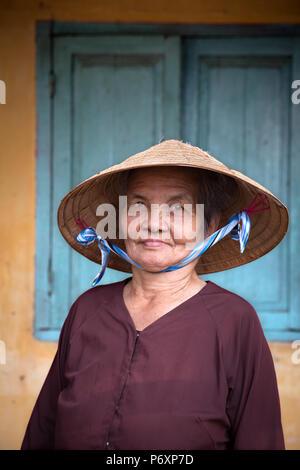 Retrato de mujer con sombrero cónico tradicional en un Binh, Vietnam