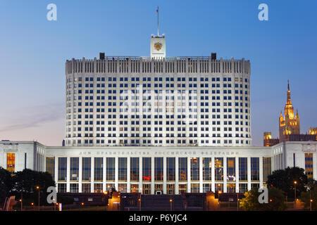 El edificio del Gobierno de la Federación de Rusia sobre la Krasnopresnenskaya Embankment encendida al anochecer. Moscú, Rusia. Foto de stock