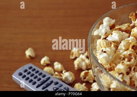Palomitas de maíz en un recipiente junto a un mando a distancia de TV