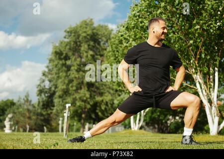 Atractiva joven hombre de negro sportwear haciendo estocada al aire libre en el parque. Foto de stock
