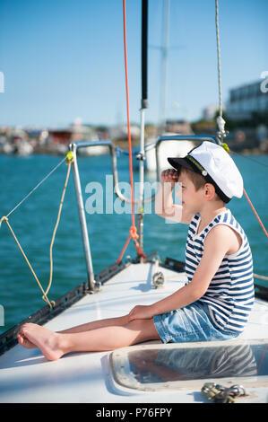 Cute little kid en capitán cap mirar a lo lejos sosteniendo la mano por  encima de 81abcad4114