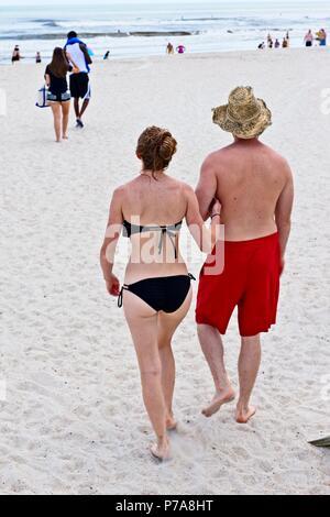 Un par camina del brazo en una playa de arena Foto de stock