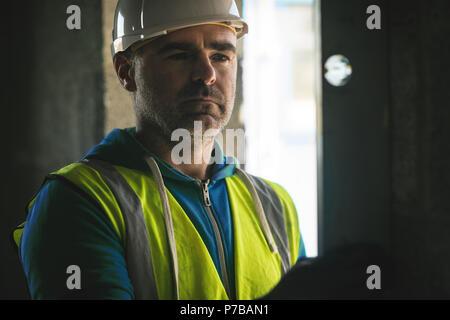 Realizando una comprobación del nivel de ingeniero en la pared en el sitio de construcción