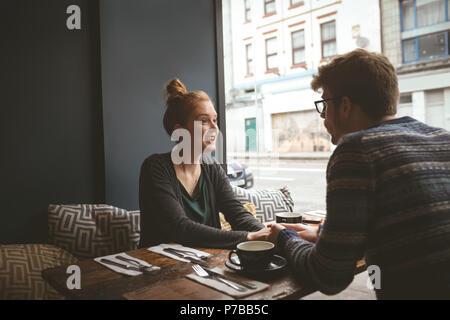 Las manos de la pareja en la cafetería