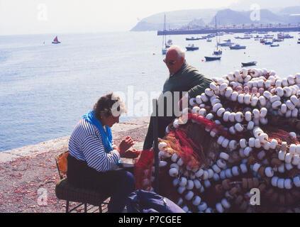 Mujer cosiendo redes de pesca en el puerto. Castro Urdiales, Cantabria, España.