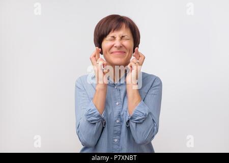 Retrato de estudio de atractiva mujer madura haber entusiasmado, supersticioso y mirada ingenua, manteniendo los dedos cruzados