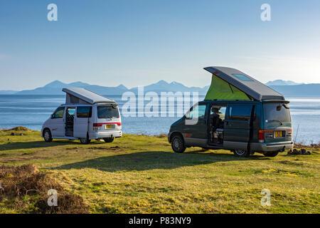 Dos Mazda Bongo campervans en la carretera costera cerca de Applecross, región de tierras altas, Escocia, Reino Unido. Mirando hacia las colinas Cuillin de Skye.