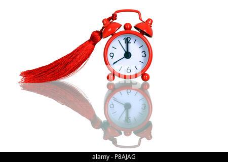 Antiguo reloj despertador rojo con borla, reloj alarma redonda roja muestra 5 minutos para la medianoche