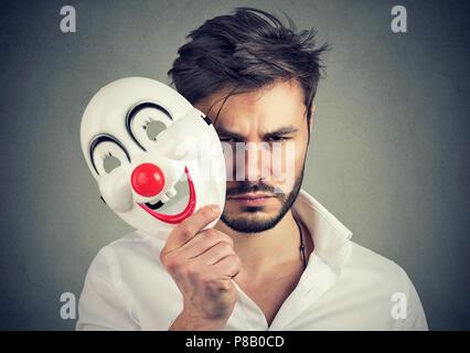 Joven barbudo hombre sujetando máscaras felices y sentirse triste y sombrío mientras mirando a la cámara sobre fondo gris Foto de stock