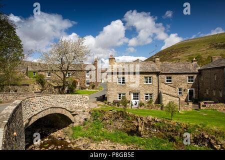 Reino Unido, Inglaterra, Yorkshire, Swaledale, Thwaite, casas del pueblo por el puente a través de la cuba de tintura de paja