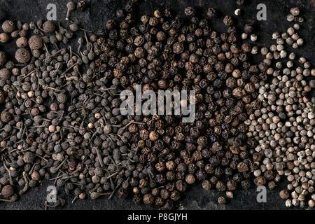 Variedad de pimiento negro pimienta de Jamaica, pimiento, monjes, los granos de pimienta pimienta negra de hierro antiguo sobre la textura de la superficie. Fondo de alimentos. Vista superior, el espacio.