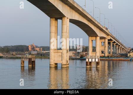 Khulna, Bangladesh, 1 de marzo de 2017: El moderno puente de hormigón en la luz de la tarde conduce a lo largo de un río en Bangladesh
