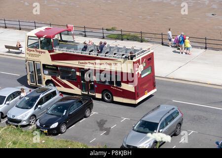 Abrir double deck autobús viaja a lo largo de la promenade road en North Bay, Scarborough, Yorkshire, Reino Unido con la gente caminando en la PROM y coches aparcados delante