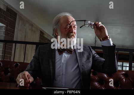 Macho viejo tratando de mirar a través de las sucias gafas. jubilado se está secando vasos. viejo hombre elegante con vista débil