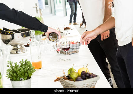 Verter el vino tinto Cristal camarero a dos hombres en blanco mesa buffet