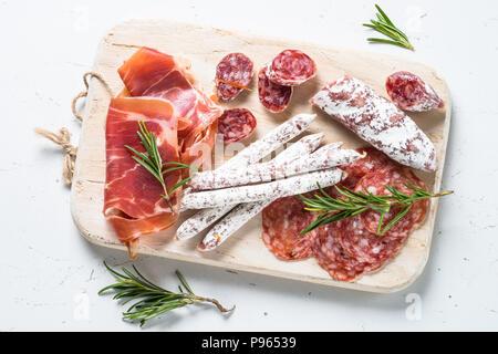 El antipasto. Antipasto italiano tradicional, lonchas de carne, aperitivo en la tabla de cortar de madera blanca sobre tabla, vista desde arriba. Foto de stock
