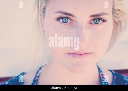 Retrato de desenfoque con foco en los ojos claros de una hermosa chica joven modelo ruso del Cáucaso sentarse y mirar a usted en la cámara. sonrisa relajarse