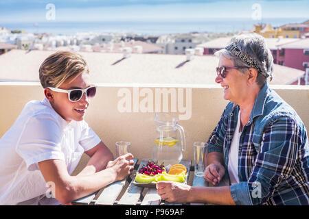 Actividad de ocio feliz en la terraza azotea desayunando con sonrisas y felicidad para la abuela y adolescente familia Pueblo Caucasiano un océano.