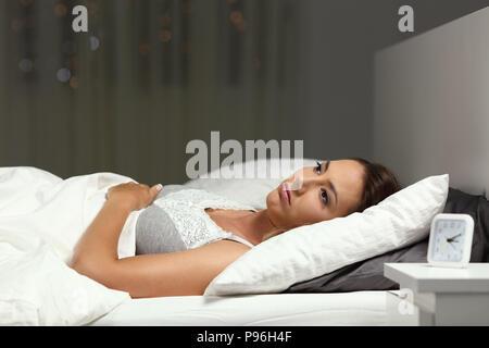 Insomniac mujer incapaz de dormir acostado en una cama en la noche en su domicilio.