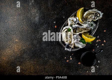 Frescos mariscos crudos, ostras con limón y hielo sobre un fondo azul claro