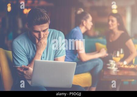 Atractivo macho es utilizando un ordenador portátil y hacer notas mientras trabaja en el cafe