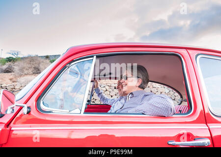 Pareja de ancianos con sombrero, con gafas, con el pelo blanco y gris, con camisa casual, en vintage coche rojo en vacaciones disfrutando de tiempo y vida. Con un chee
