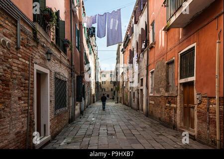 Un hombre que camina sobre una calle casi vacía en el secado de la ropa de cama en Venecia, Italia